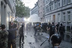 Demonstrierende setzten sich mit Schildern und Brettern gegen den Wasserwerfer zur wehr bzw. greifen diesen an im Schanzenviertel.