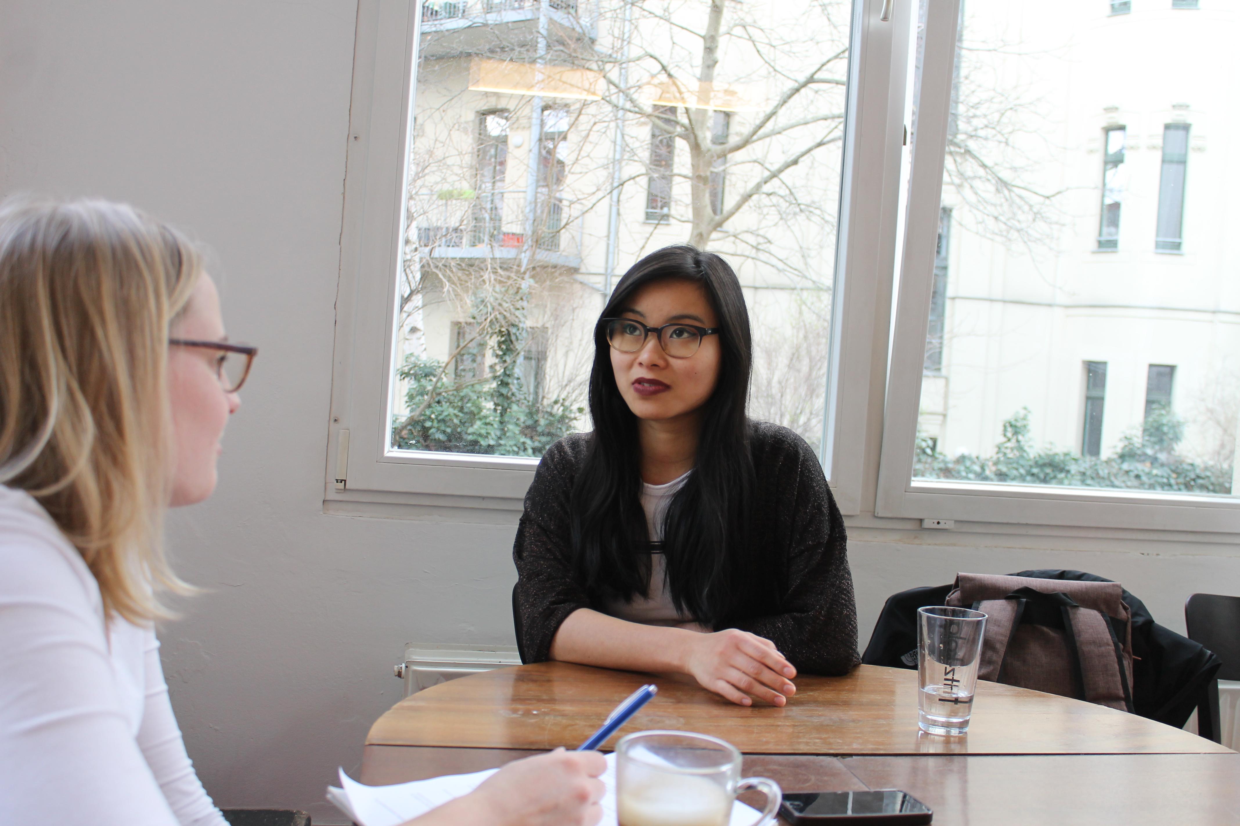 Bloggerin Nhi Le sitzt an einem Tisch; links im Bild student!-Redakteurin Hanna Lohoff