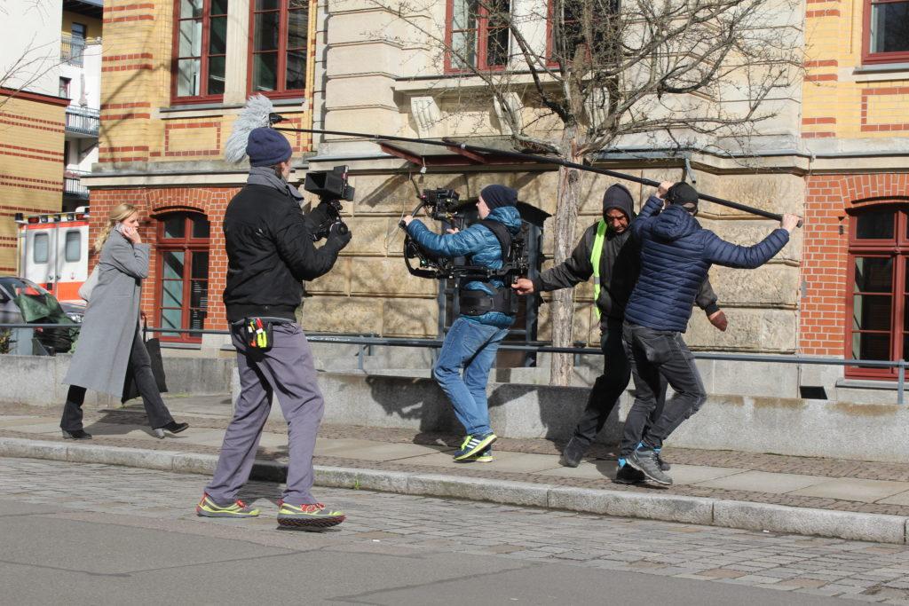 Eine Frau und mehrere Kamera- und Tonmänner.