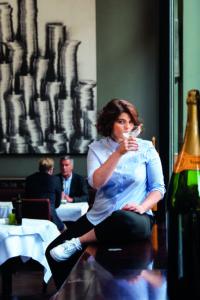 Autorin Sophie Passmann sitzt in einem Café mit einem Glas in der Hand.