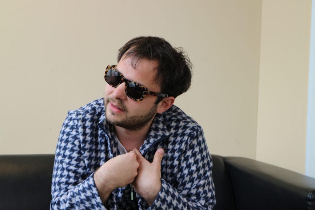 Peter Horazdoysky von der Band Bilderbuch sitzt in seiner Garderobe und trägt eine Sonnenbrille.