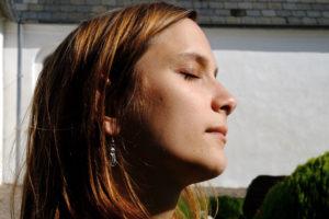 Redakteurin Pauline schaut mit geschlossenen Augen in die Sonne