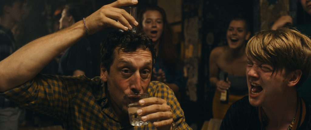 Ein dunkelhaariger Mann im gelben Karohemd hält ein Glas auf dem Kopf und eins am Mund, ein Blonder neben ihm hat den Mund geöffnet.