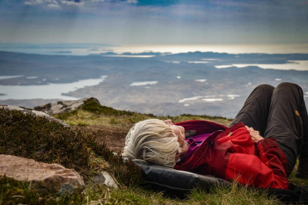 Eine Frau liegt auf der Kuppe eines Berges und schaut in den Himmel