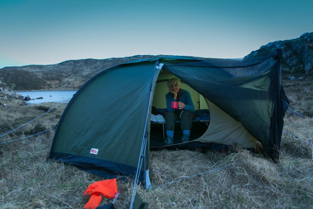 Eine Frau sitzt in einem Zelt vor einem See