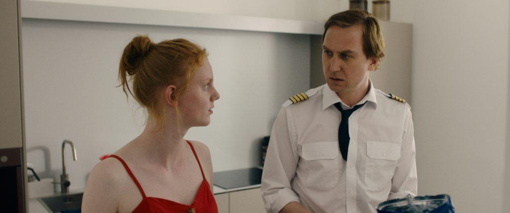 Ein Mann in Uniform und ein rothaariges Mädchen in rotem Kleid schauen sich an.