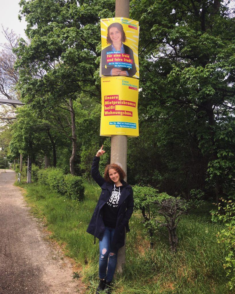 Junge Frau stehend unter zwei Wahlplakaten der FDP.