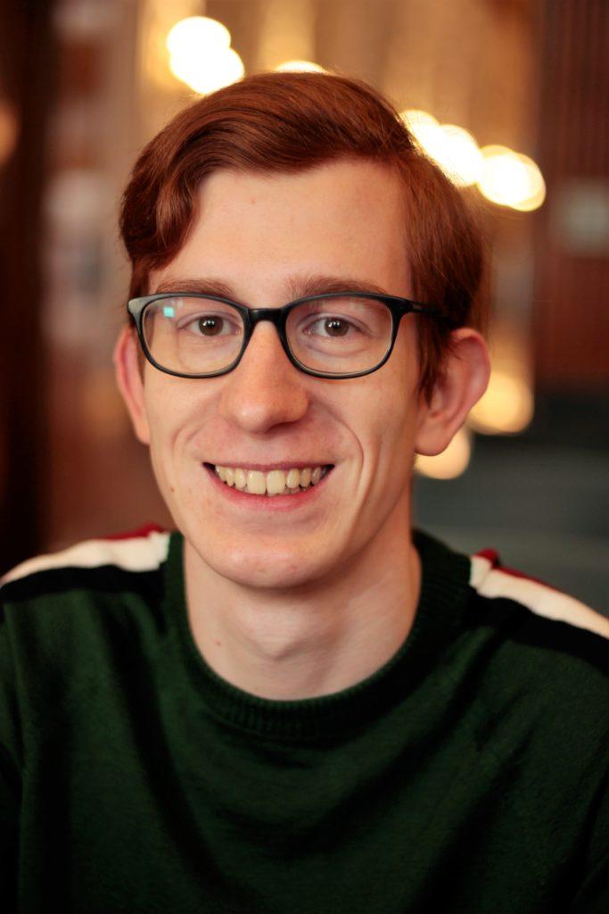 Ein junger Mann mit rötlichen Haaren und Brille.