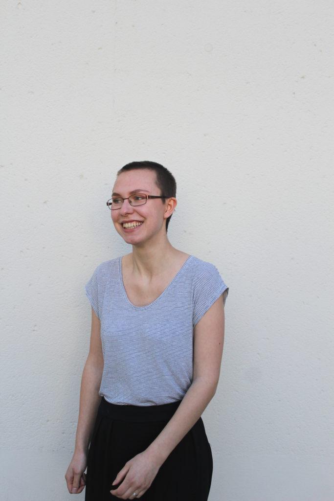 Porträtbild der Kolumnistin Annika Seiferlein. Sie lacht und draußen scheint es warm zu sein.
