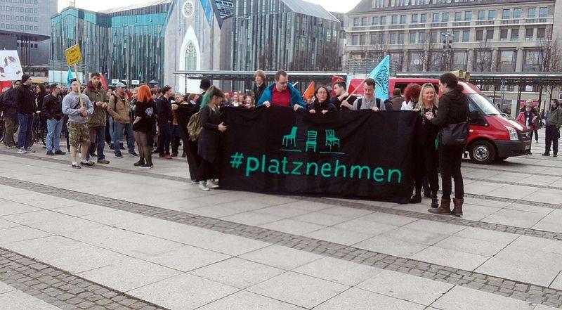 Mehrere Demonstrierende am Leipziger Augustusplatz mit einem Banner vom Aktionsnetzwerk Leipzig nimmt Platz.