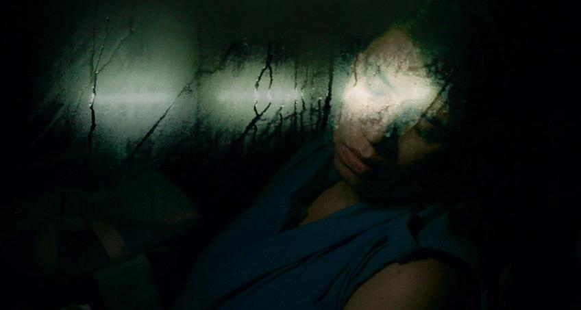 Eine junge Frau schläft in einem Bus, ihr Kopf lehnt am Fenster. Sie trägt ein blaues Oberteil. Es ist sehr dunkel, das einzige Licht der Neonröhren verschwimmt in der beschlagenen Scheibe.