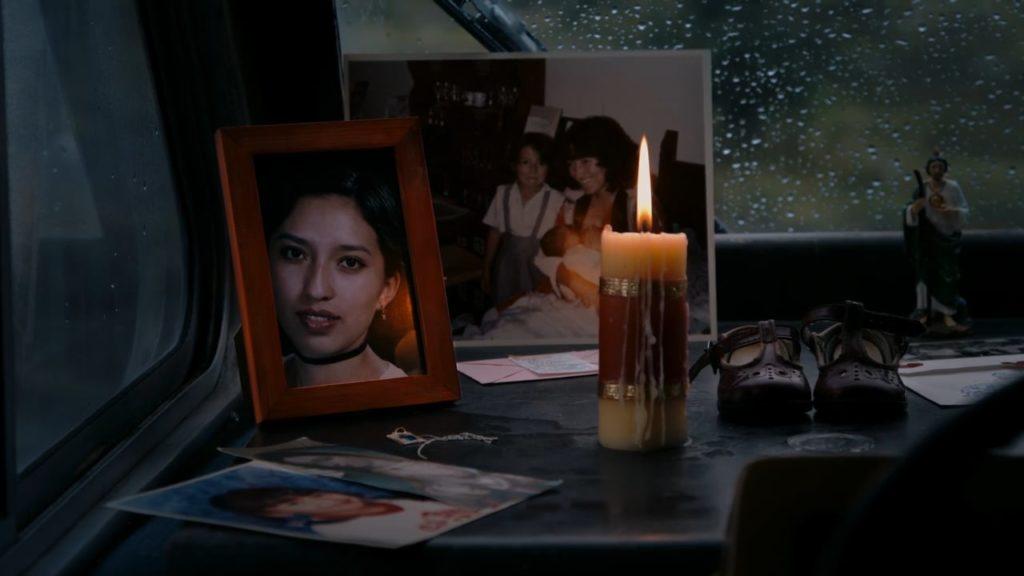 Auf einer Ablage am Fenster des Wohnwagens stehen mehrere Fotos von Monica, als Kind und als junge Frau, sowie eine brennende Kerze, ein paar Babyschuhe und eine Heiligenfigur.