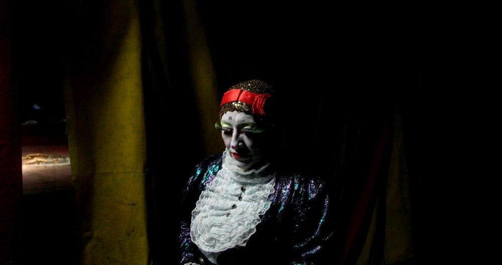 Adelas weiß geschminktes Gesicht im Spiegel, man sieht es nur zur Hälfte. Die Haare hat sie mit einer dunkelroten Mütze zurückgehalten. Sie trägt ein weißes Oberteil und blickt nach unten, im Hintergrund um den Spiegel eine dunkelblaue Wand.