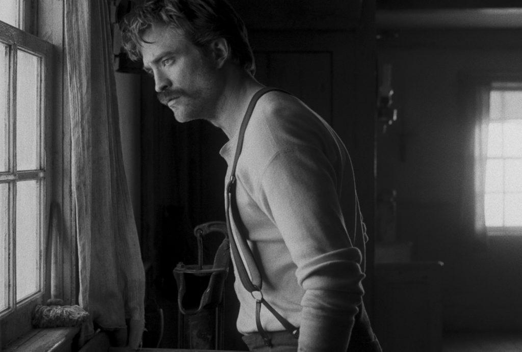 Robert Pattinson alias Ephraim Winslow schaut besorgt aus dem Fenster des Wärterhäuschens. Er trägt eine Hose mit Hosenträgern und einen für die 1900er Jahre typischen Schnauzer.