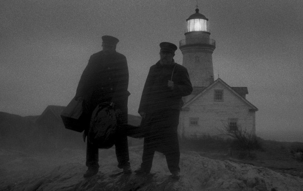 Willem Dafoe alias Tom Wake (rechts im Bild) und Robert Pattinson alias Ephraim Winslow (links im Bild) trotzen dem heftigen Sturm auf einem Felsen, während sie auf das Ablösungsboot warten, das nicht kommt.