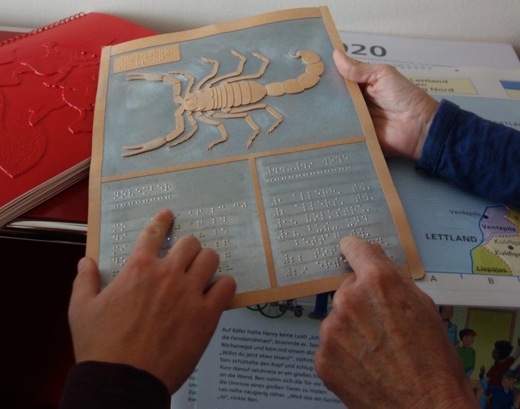 Eine Zinkplatte zum Übertragen von Brailleschrift und Hände von zwei Personen, die sie halten.