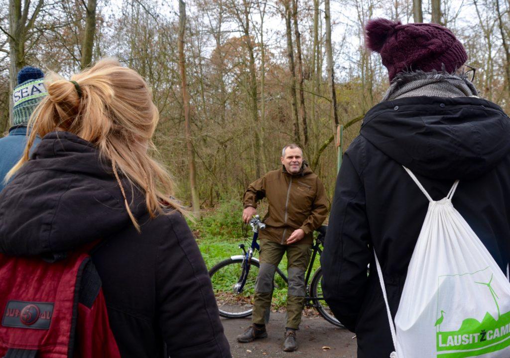 Das Bild zeigt den Revierförster Thomas Knorr. Er steht vor einer Gruppe von Studierenden auf einem Waldweg und ist auf sein Fahrrad gelehnt.