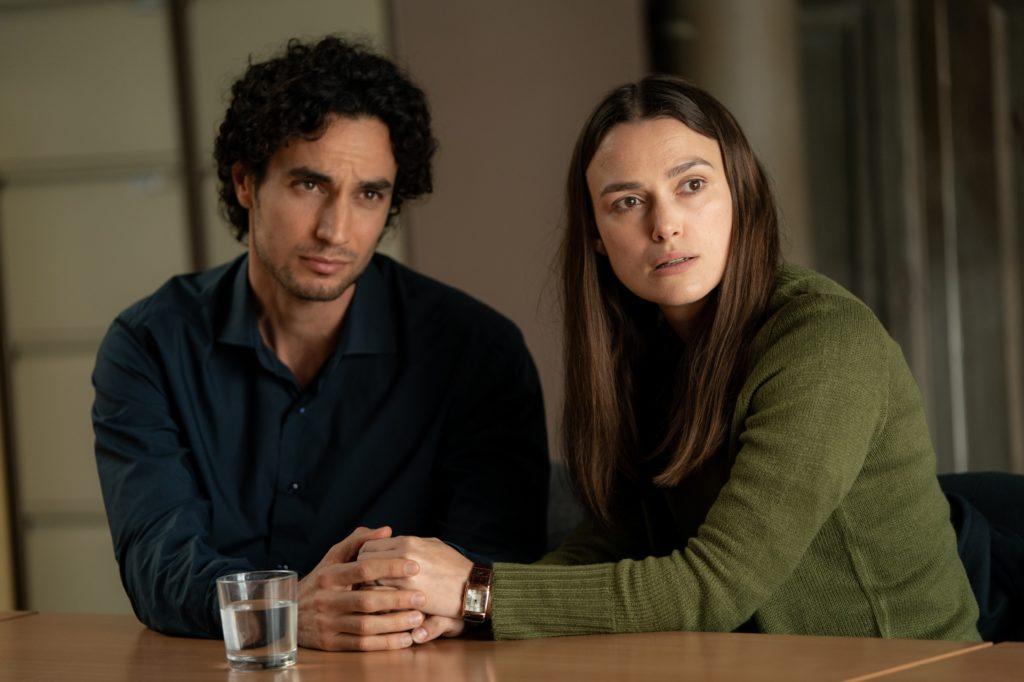 Katharine Gun (Keira Knightley) und ihr Mann Yasar (Adam Bakri) sitzen am Tisch und halten besorgt die Hände des anderen.