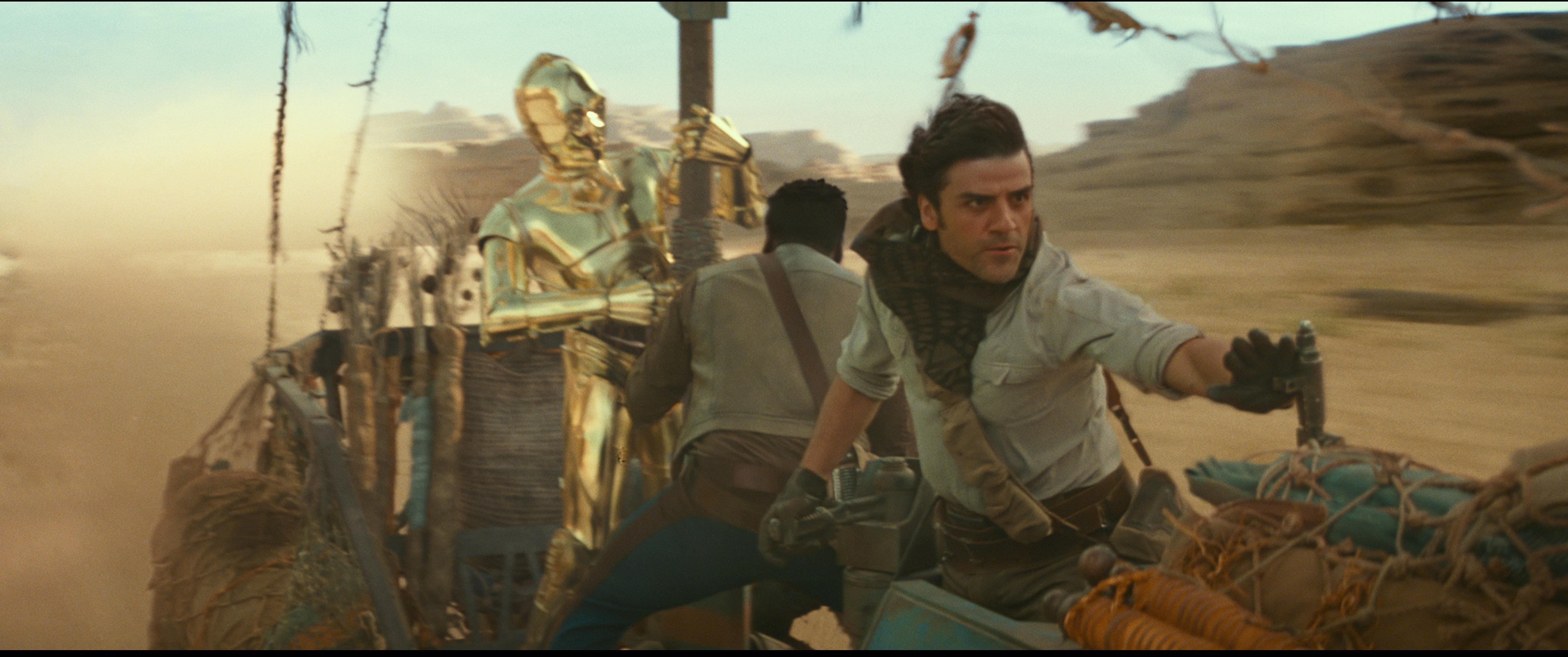 Die Filmfiguren Finn, gespielt von John Boyega, und Poe, gespielt von Oscar Isaac, mit C3PO auf einem Gefährt.