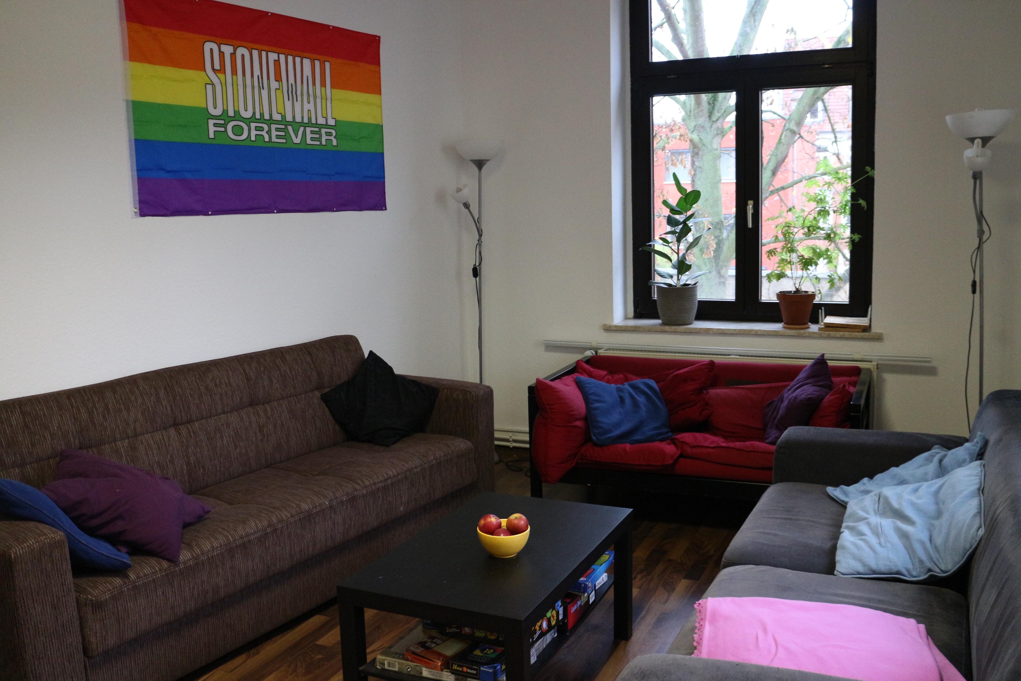 """Das Bild zeigt das Wohnzimmer des Rosalinde Vereins. Im Bild sind ein braunes und ein rotes Sofa, ein kleiner Tisch sowie eine Regenbogen-Flagge mit der Aufschrift """"Stonewall Forever"""" an der Wand."""