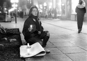 Alternativtext: Eine junge Frau mit erschrockenem Ausdruck sitzt in einer Fußgängerzone auf dem Boden. Sie hält eine Kerze in der Hand, neben ihr stehen zwei weitere, im Hintergrund Passanten.