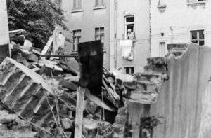 : Im Vordergrund ein Haufen von Trümmern und Schutt, ein Stück Mauer steht noch. Dahinter hängt eine Frau auf der Leine vor ihrem Fenster Wäsche auf.