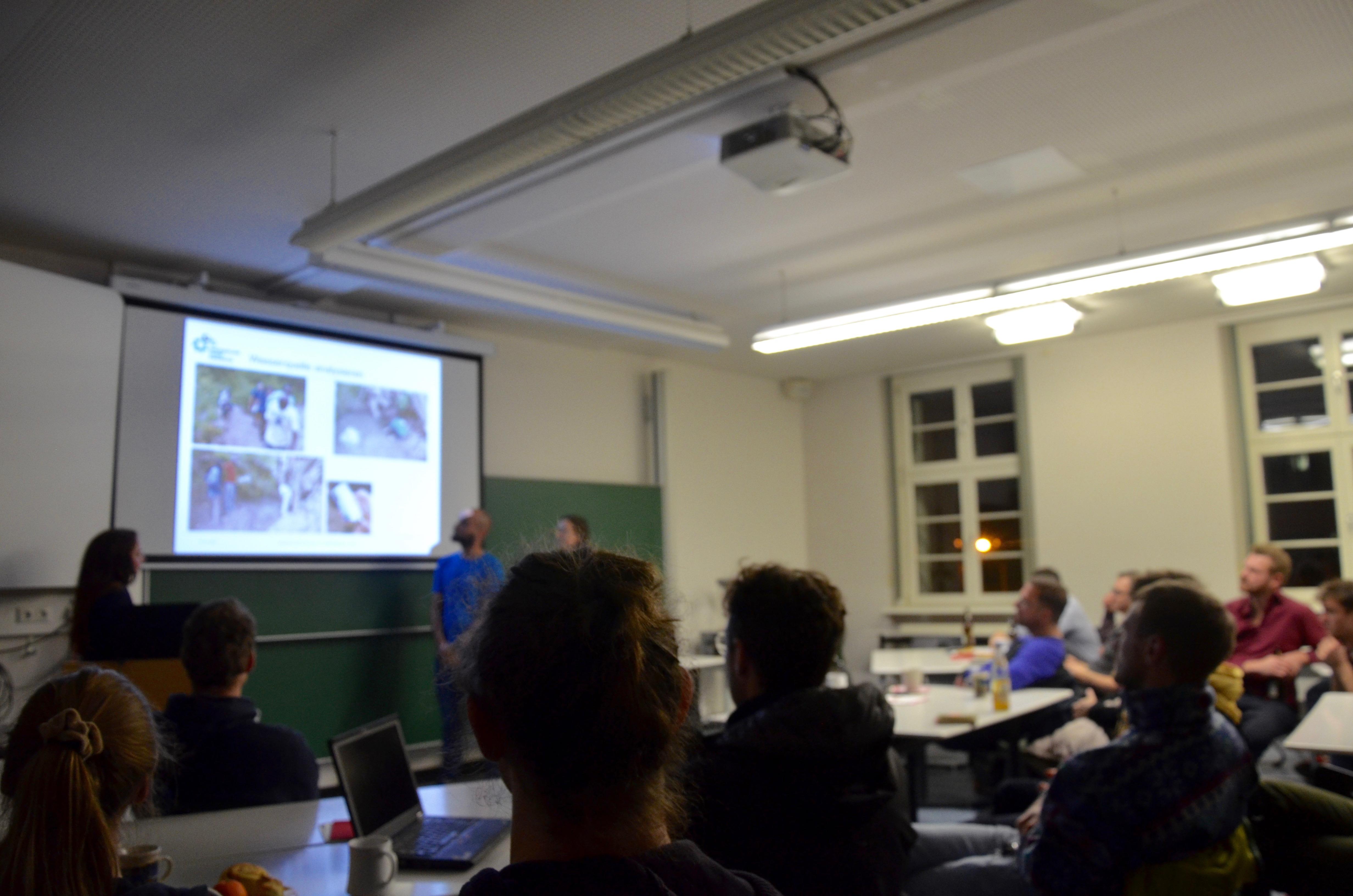 Das Bild zeigt einen im schwachen Neonröhrenlicht erleuchteten Seminarraum. Drei Personen von Ingenieure ohne Grenzen Leipzig zeigen im Hintergrund eine Bildschirmpräsentation. Im Vordergrund sind die Hinterköpfe von Menschen zu sehen, die ihnen zuhören.