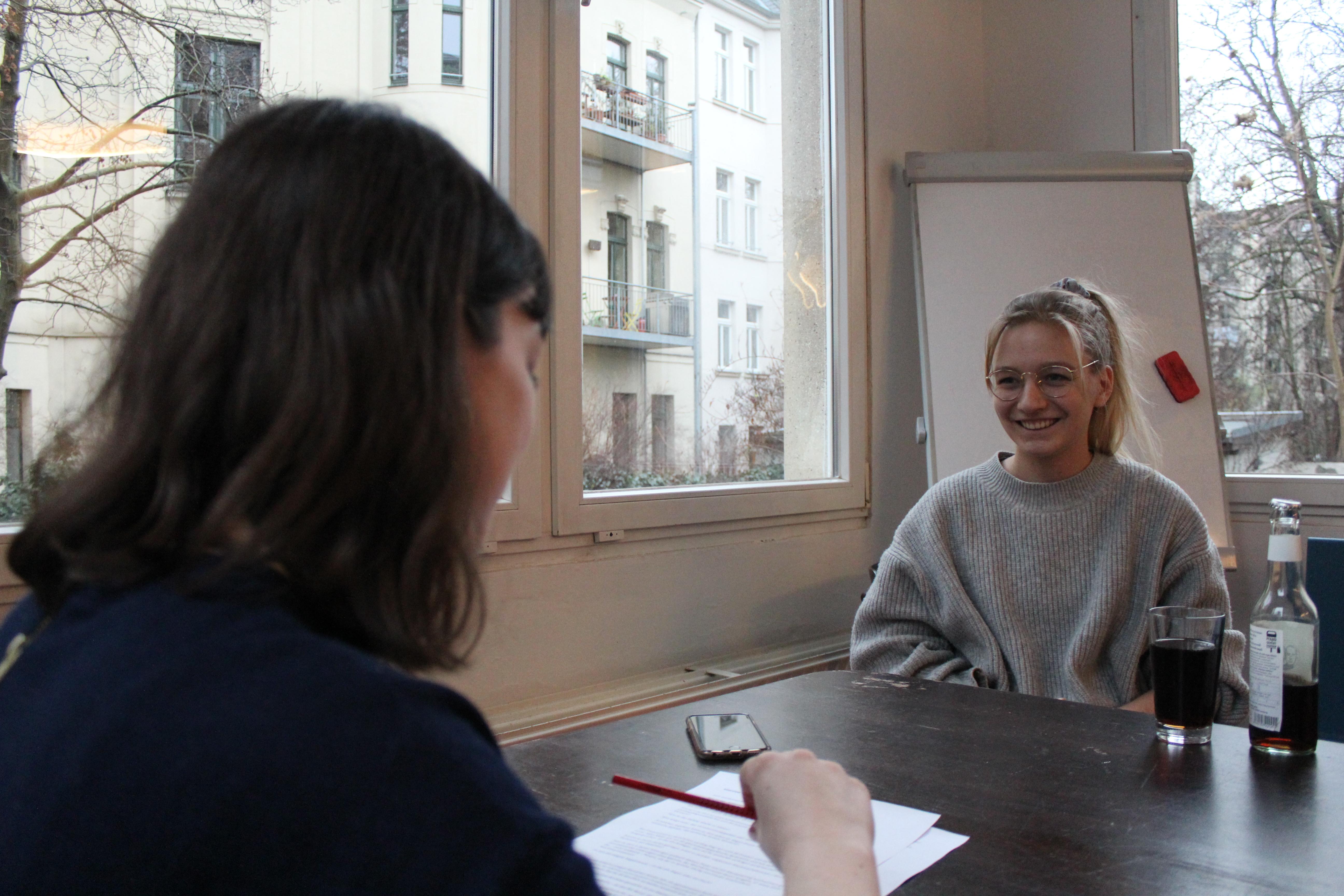 Das Bild zeigt zwei Frauen in einer Interview-Situation an einem Tisch. Auf der einen Seite sitzt Lucie Hammecke, grinsend. Auf der anderen Seite sitzt luhze-Redakteurin Sophie Goldau mit einem Stift und den ausgedruckten Interviewfragen auf dem Tisch.