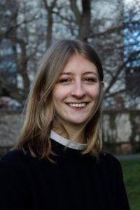 Das Foto zeigt die Kolumnistin Lisa in Nahaufnahme. Sie steht auf einer Wiese und trägt einen schwarzen Pullover. Sie lächelt in die Kamera.