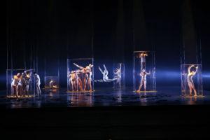 Auf der Bühne sind Tänzerinnen und Tänzer in Glasquader eingeschlossen.