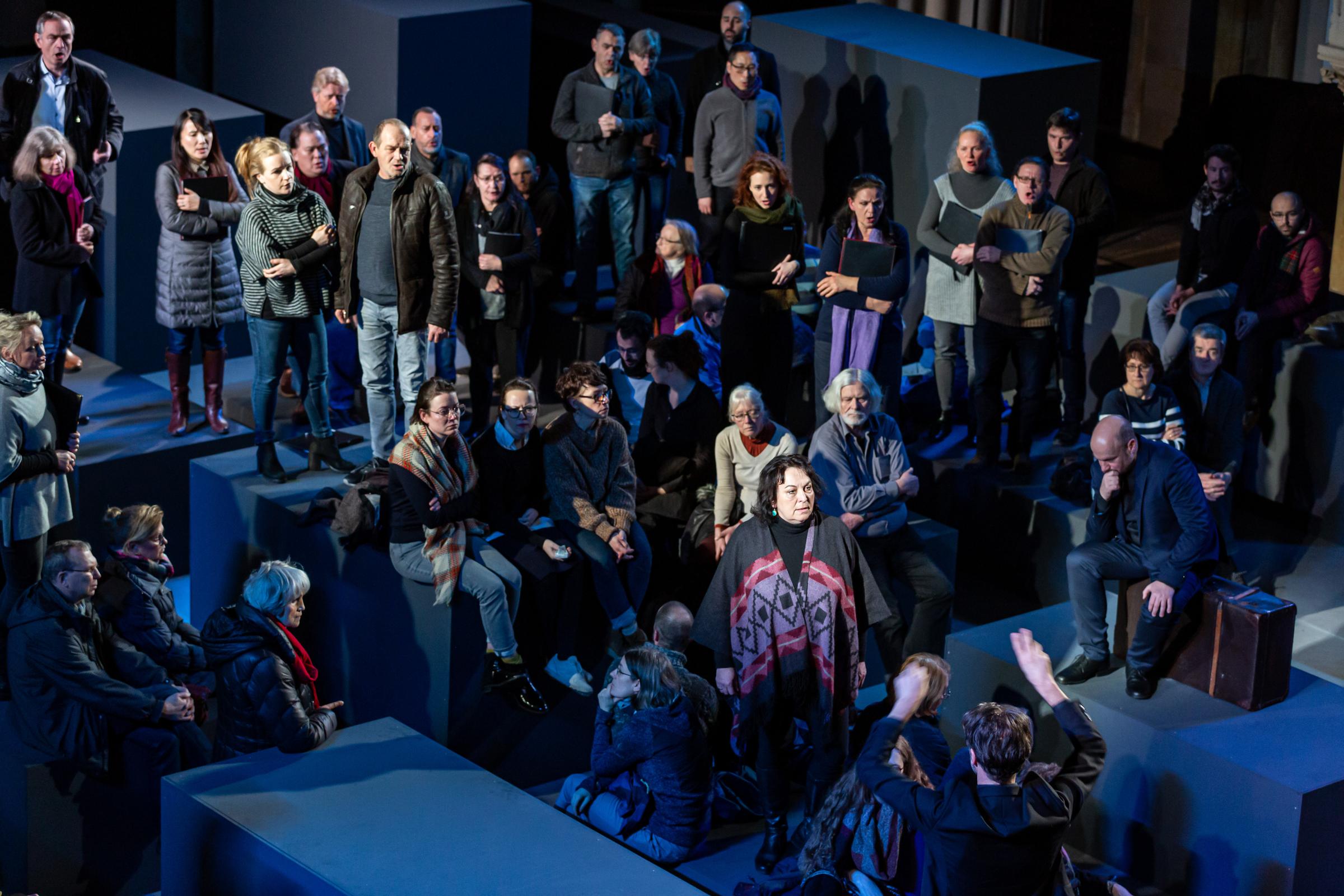 Das Foto wurde von oben aufgenommen. Man sieht das Publikum und vereinzelt dazwischen die Chromitglieder, erkennbar an ihren schwarzen Mappen.
