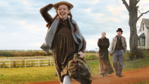 Freudestrahlend macht sich Anne an ihrem ersten Schultag auf den Weg. Die Cuthberts sind im Hintergrund vor ihrem Hofs sehen.