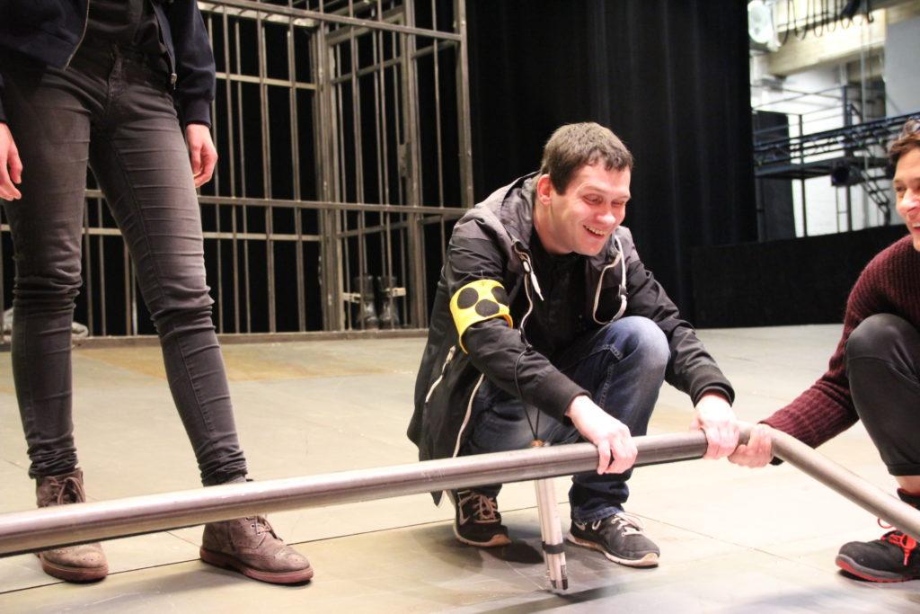 Dennis ertastet knieend die Eisenstange, die die Bühne zum Publikum hin abgrenzt.