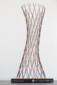 Der Prototyp, den sie auf der internationalen Handelsmesse in München präsentiert haben. Der Prototyp ist höher als sie, schwingt sich elegant in die Höhe und besteht aus schwarzen Strohhalmen aus Papier, die mit orangefarbenen Verbindungselementen verbunden sind.