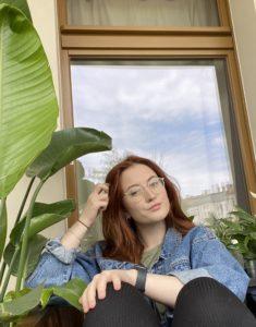Die Kolumnistin vor einem Fenster sitzend und in die Kamera blickend. Sie hat rotbraune Haare und ein blaues Hemd