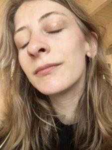 Das Bild zeigt die Kolumnistin Lisa auf einem Selfie. Die Sonne scheint ihr ins Gesicht, die hat die Augen geschlossen und den Kopf in leicht geneigt.
