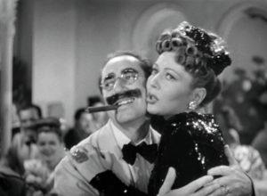 Hühnerpuster drückt eine Dame beim Tanzen an sich. Er trägt einen übergroßen Schnauzbart und raucht eine Zigarre