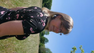 Die Kolumnistin in einem schwazen Shirt im Gras