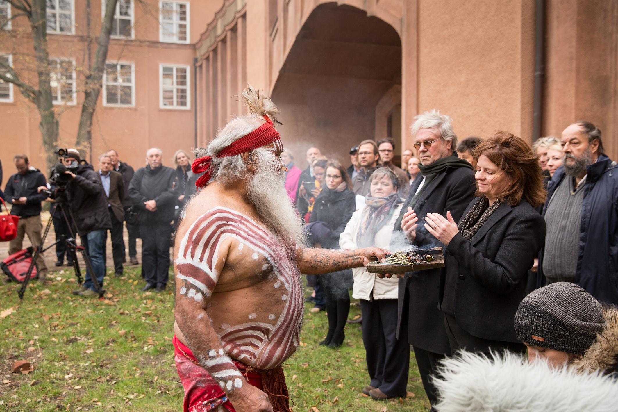 Ein Mitglied einer australischen Community steht mit rot-weiß bemaltem Oberkörper und langem, weißem Bart vor Grassi Museumsdirektorin Leontine Meijer-van Mensch mit einem rauchenden Stück Holz in der Hand. Um sie herum stehen Menschen.