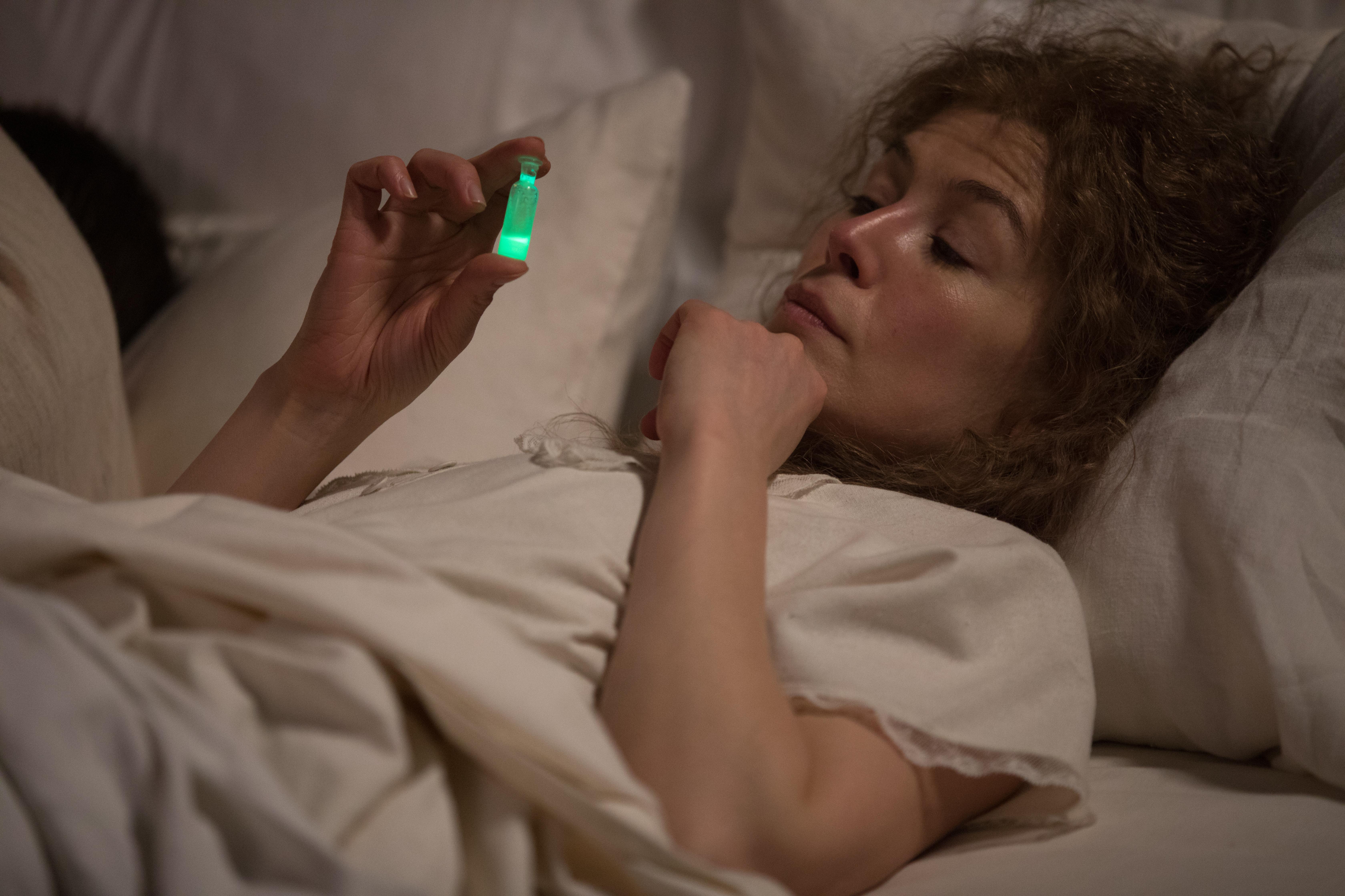 Die Schauspielerin Rosamund Pike spielt Marie Curie. Die blonde Frau liegt im weißen Nachthemd im Bett und betrachtet vertieft ein kleines Fläschchen mit einer leuchtend grünen Flüssigkeit darin.