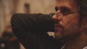 Christoph Schlingensief ist im Profil vor einem dunklen Hintergrund zu sehen. Sein Gesicht ist mit warmem Licht beleuchtet und er blickt aufmerksam auf einen Punkt hinter dem linken Bildrahmen.