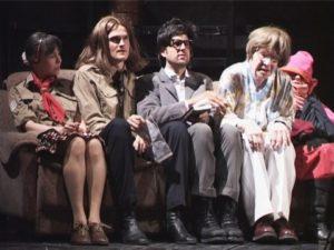 Auf dem Bild sieht man Schlingensief, der auf einer Coach auf einer Theaterbühne sitzt. Rechts und links neben ihm sitzen noch jeweils zwei andere Schauspieler*innen. Alle tragen Kostüme, Christoph Schlingensief eine schwarze Perücke und Brille mit einem klobigen Rahmen.