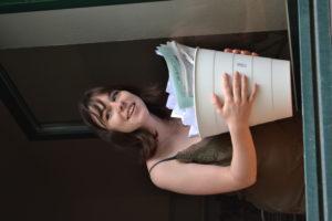 Kolumnistin Sophie mit einem Mülleimer in der Hand schaut aus dem geöffneten Fenster
