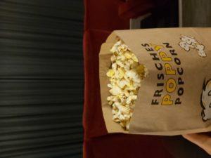 Man sieht eine Packung Popcorn, im Hintergrund einen zugezogenen Kinovorhang