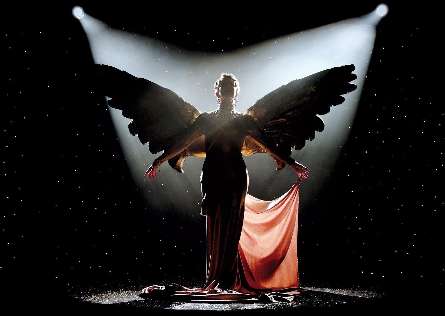 Werbebildschirm mit Foster Jenkins, schwarz-weiß Aufnahme, sie trägt enges, langes Kleid mit großen Engelsflügeln.