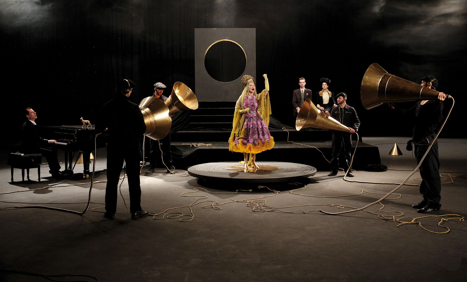 Frau in golden pinkem Kleid steht auf Podest und singt. Drumherum stehen Menschen in Anzügen und halten große, goldene Trichter in ihre Richtung.