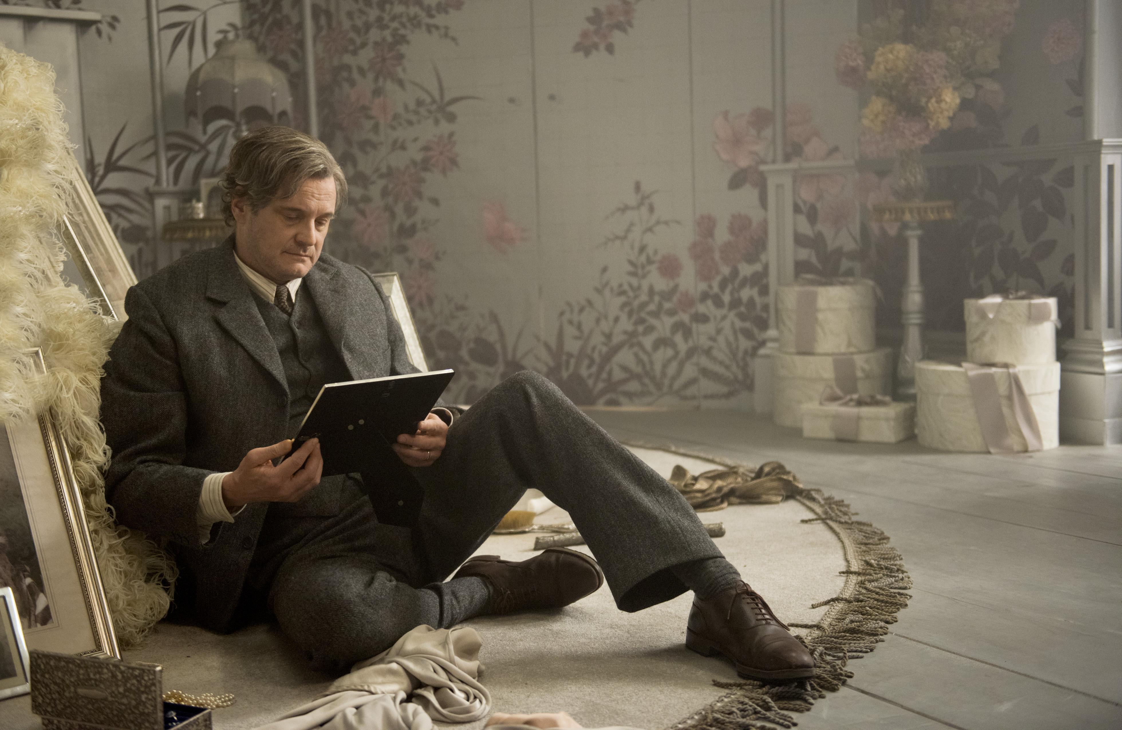 Colin Firth alias Lord Archibald sitzt in einem verstaubten, grauen Zimmer auf dem Boden und schaut mit liebevollem Blick auf ein Foto, scheinbar von seiner verstorbenen Frau.