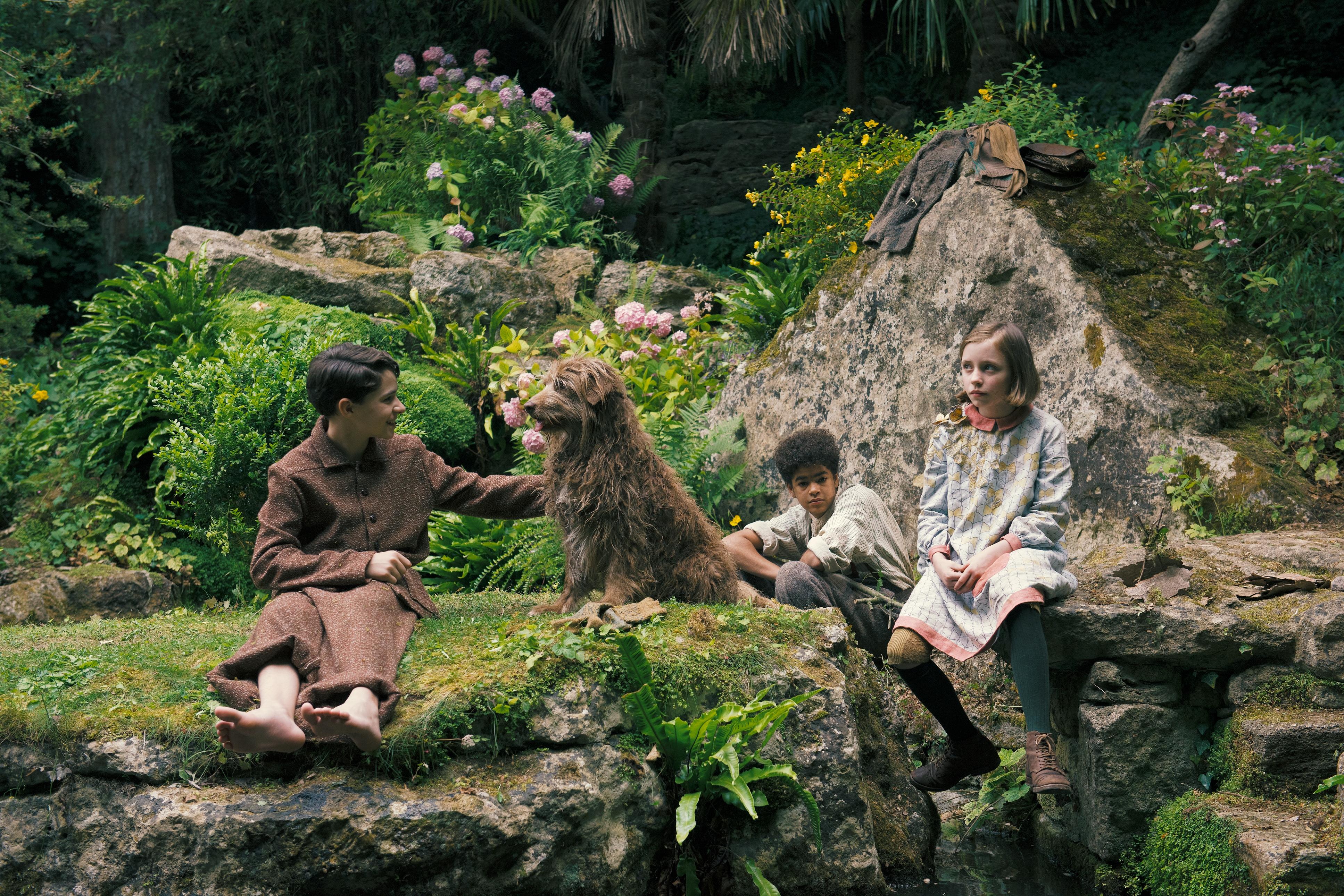 Colin (Edan Hayhurst), Dickon (Amir Wilson), Mary (Dixie Egerickx) und der im Garten lebende Streunerhund genießen den Tag im geheimen Garten.