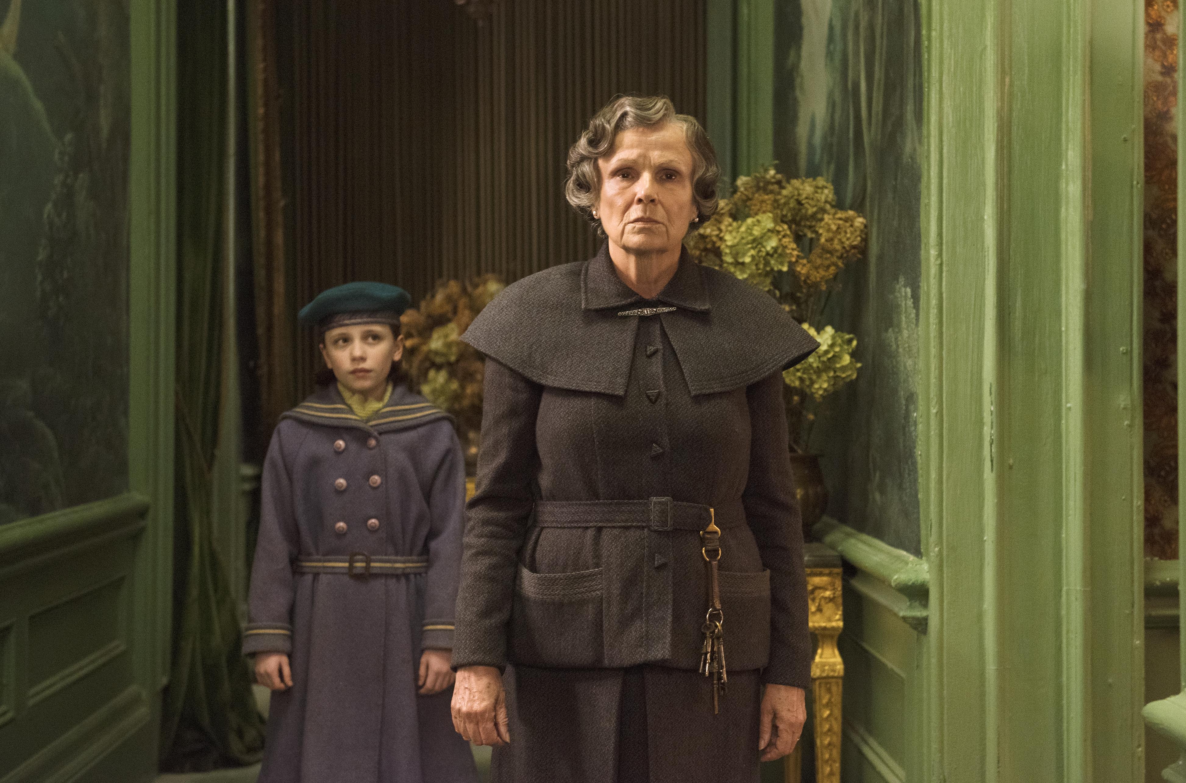 Im Vordergrund steht die ebenso streng frisierte wie streng wirkende Haushälterin Mrs. Medlock (gespielt von Julie Walters), im Hintergrund steht das Waisenmädchen Mary (Dixie Egerickx) und blickt erwartungsvoll und leicht eingeschüchtert auf Mrs. Medlock.