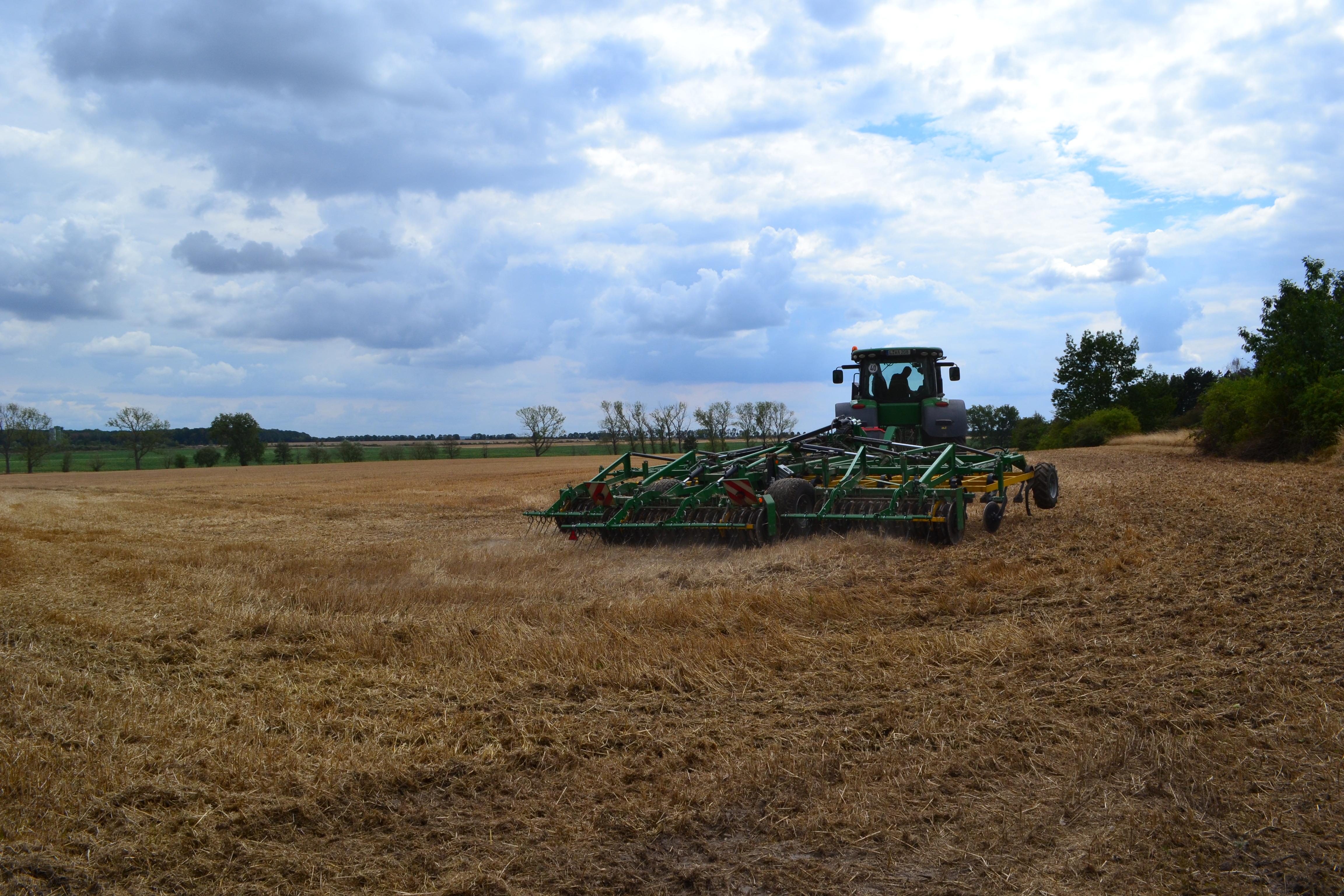 Ein Traktor fährt über ein Feld mit einem Stoppelstürzer